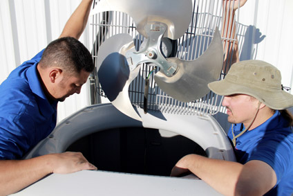 Repair technicians working on an air conditioner