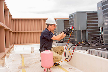 Air conditioning technician working on building.